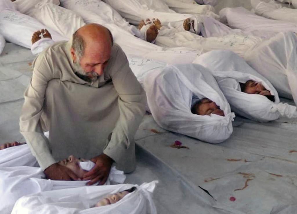 En man sörjer döda i en påstådd gasattack i Douma nära Damaskus, augusti 2013. Foto: AP