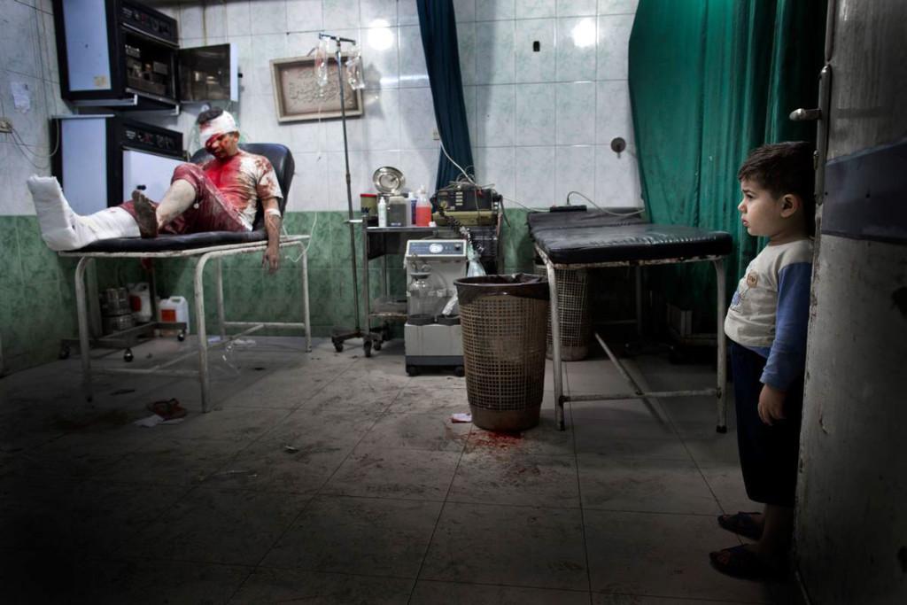 En liten pojke tittar på en skadad man i en av  Dar al-Shifa-sjukhusets operationssalar. Foto: NICLAS HAMMARSTRÖM