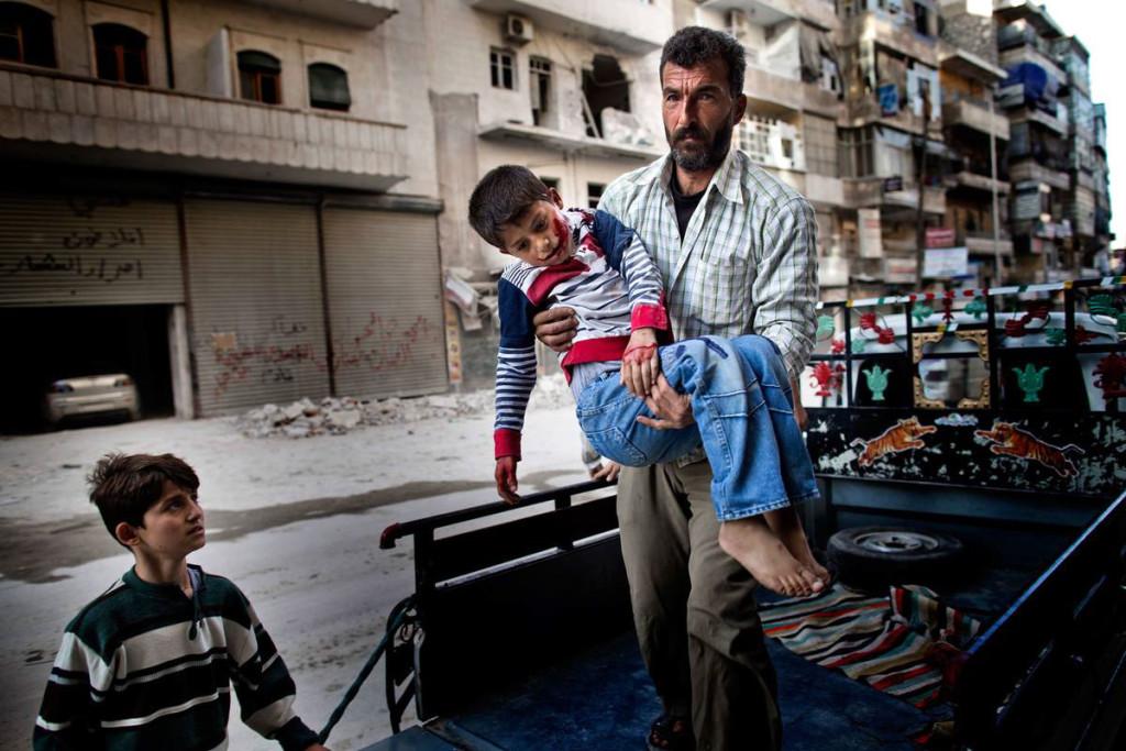 Sexårige Mustafa bärs in på sjukhuset i Aleppo av sin far. Mustafa var ute och lekte med sin kusin när han träffades av splitter från en granat. Foto: NICLAS HAMMARSTRÖM